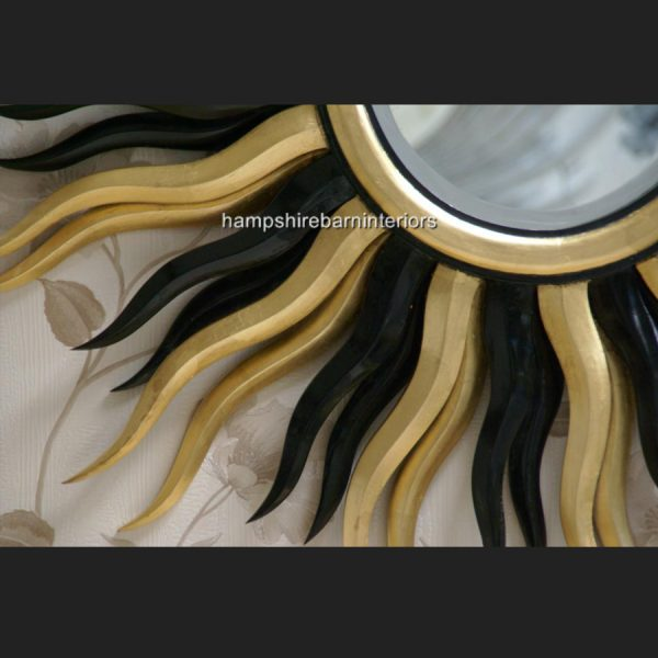 A Designers Large Star burst mirror in gold and black2